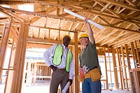 Builder in hardhat pointing up to businessman in partially built house, low angle view