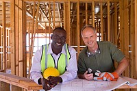 Businessman and builder with blueprints in partially built house, smiling, portrait