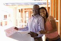 Young couple with blueprints in partially built house, smiling, portrait (thumbnail)