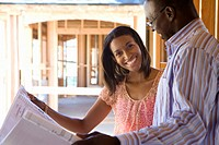 Young couple with blueprints in partially built house, smiling