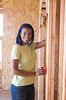 Woman measuring wall in partially built house, smiling, portrait