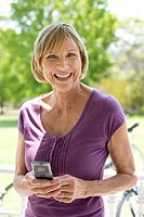 Mature woman with mobile phone, bicycle in background, smiling, portrait