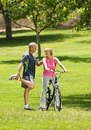 Mature man stretching with hand on shoulder of woman on bicycle, smiling