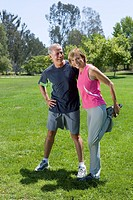 Mature couple exercising in park, woman stretching, portrait