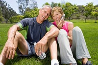 Mature couple sitting in park with water bottles, smiling, portrait