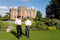 Young man in conversation with friend in gardens of manor house