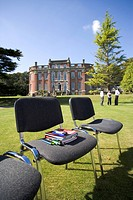 Books and pens on chair on grass by manor house (thumbnail)