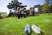 Water bottles on grass by business people in training course by manor house (thumbnail)