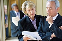 Mature businesswoman showing paperwork to colleague, close-up