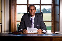 Mature businessman at desk with paperwork, portrait (thumbnail)