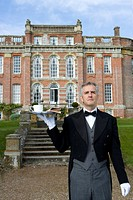 Mature butler with tray of tea by manor house, low angle view