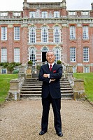 Mature businessman with arms crossed in front of manor house, portrait