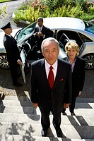 Businessman and colleagues by car, chauffeur holding door open, portrait