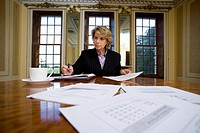 Businesswoman with paperwork at table