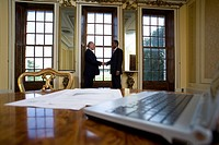 Laptop computer and paperwork on table, businessmen shaking hands in background, differential focus