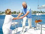 Senior man helping woman onto boat, smiling
