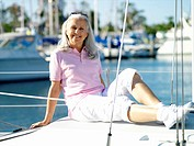 Mature woman reclining on deck of boat, smiling, portrait