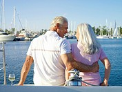 Mature couple on deck of boat, man with arm around woman, rear view