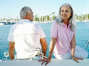 Mature couple on deck of boat, smiling