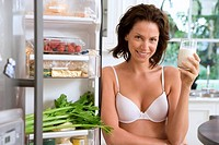 Young woman in underwear with drink by open door of fridge, smiling, portrait