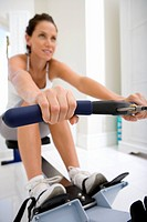 Young woman on rowing machine, low angle view