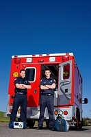 Paramedic and colleague with arms crossed by open door of ambulance, portrait, low angle view