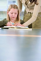 Mother helping daughter 7-9 with homework