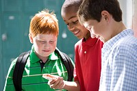 Boy 10-12 showing friends mobile phone, smiling