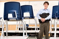 Teacher with bag in classroom by chairs on desks, smiling, portrait