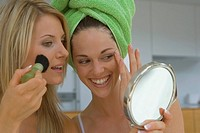 Two women with make-up brush and hand mirror