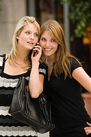Young women listening to cell phone together (thumbnail)