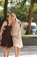 Portrait of happy women outdoors and woman pointing (thumbnail)