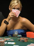 Woman holding up playing cards at poker game