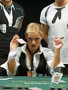 Woman with cigar throwing playing cards at poker game