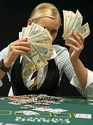 Woman holding wad of cash at poker game