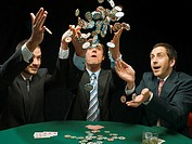 Men throwing poker chips in air