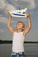 Young boy holding toy boat near lake