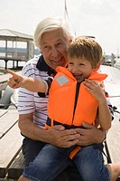 Grandfather and grandson at the lake with boy pointing