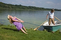 Young girl pulling boat with boy in it to shore