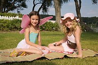 Young girls dressed up and sitting in yard (thumbnail)