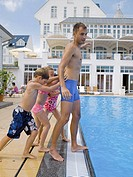 Children pushing man in pool