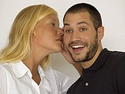 Woman whispering in man's ear (thumbnail)