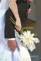 Flower detail of groom giving bride piggyback ride (thumbnail)