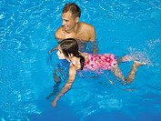 Man teaching girl how to swim