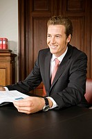 Happy businessman sitting at table