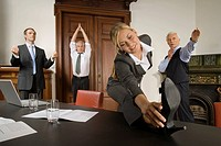 Businesspeople stretching in meeting room