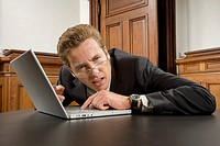 Confused businessman with laptop