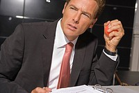 Close-up of a businessman looking serious with a file in front of him (thumbnail)