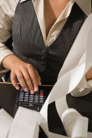 Mid section view of a businesswoman calculating on an adding machine