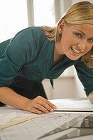 Portrait of a female architect working on a blueprint and smiling